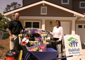 Shawn Reed, president of the Home Builders Association of the Central Coast, and Julia Ogden, CEO for San Luis Obispo Habitat for Humanity, stand with donated tools in front of one of the SLO Habitat homes.