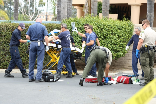 Emergency personnel tend to a woman with apparently self-inflicted ...