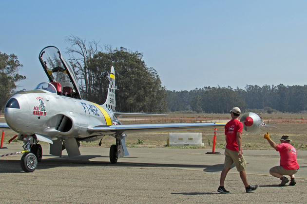A volunteer gives a thumbs up as ground crews park a vintage plane at the Santa Maria Public Airport where the Museum of Flight's Thunder Over the Valley Air Show will take place this weekend.
