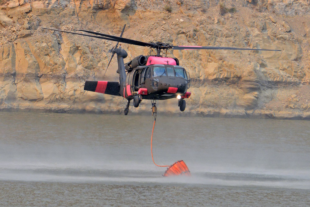 A Blackhawk helicopters draws water from Gibraltar Reservoir Monday while battling the Rey Fire in the Santa Barbara backcountry. Protecting the county's vital watersheds is a priority in fighting the blaze.