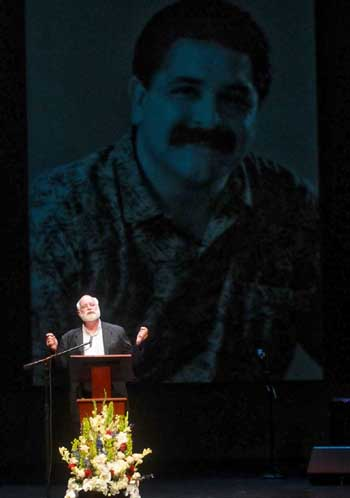 With a photo of Matt Sanchez as a backdrop, the Rev. Greg Boyle delivers the eulogy during Saturday's memorial service in The Granada Theatre. (Lara Cooper / Noozhawk photo)