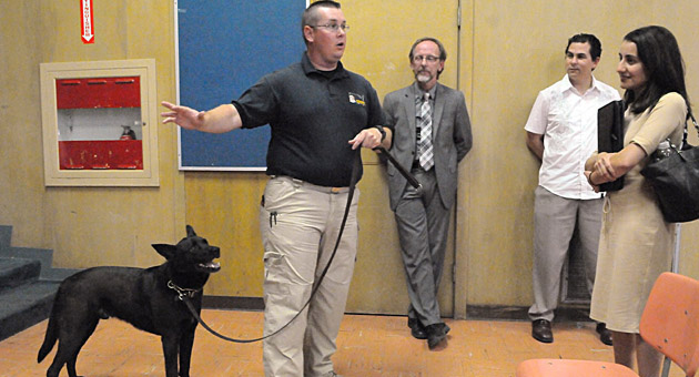 <p>Drug-detection dog Skeeter, a lab cattledog mix, stands ready as Interquest canine handler Mike Post talks to parents, officials and the media in May 2012 about how drug-detection dogs such as Skeeter would be used at Santa Barbara district high schools. On Tuesday, for the third year in a row, the Santa Barbara school board approved a contract for the program.</p>