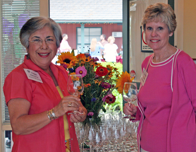 Hosts and directors Vangie Herrera and Carolyn Tulloh welcome guests with complimentary wine glasses at the Friendship Center's Second Annual Wine Down last Friday in its courtyard on Eucalyptus Lane in Montecito.