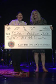 Veronica Sandoval, of the Santa Ynez Band of Chumash Indians, gives donation to Direct Relief's Alisse Harris.