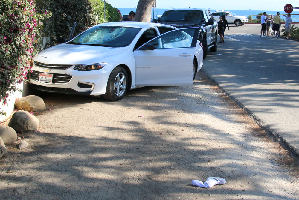 A Chevrolet Impala struck and severely injured a pedestrian in Montecito on Tuesday afternoon. In the foreground is a handgun wrapped in a sock that reportedly was discarded by the driver, who fled and remained at large Wednesday night.