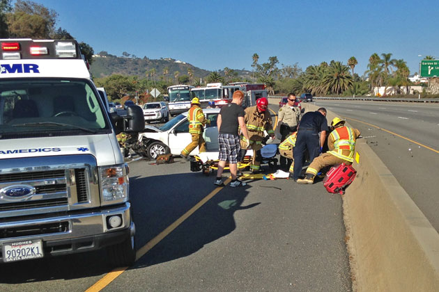 Santa Barbara firefighters and paramedics tend to a woman who was injured Sunday in a single-vehicle crash on southbound Highway 101 near Garden Street.