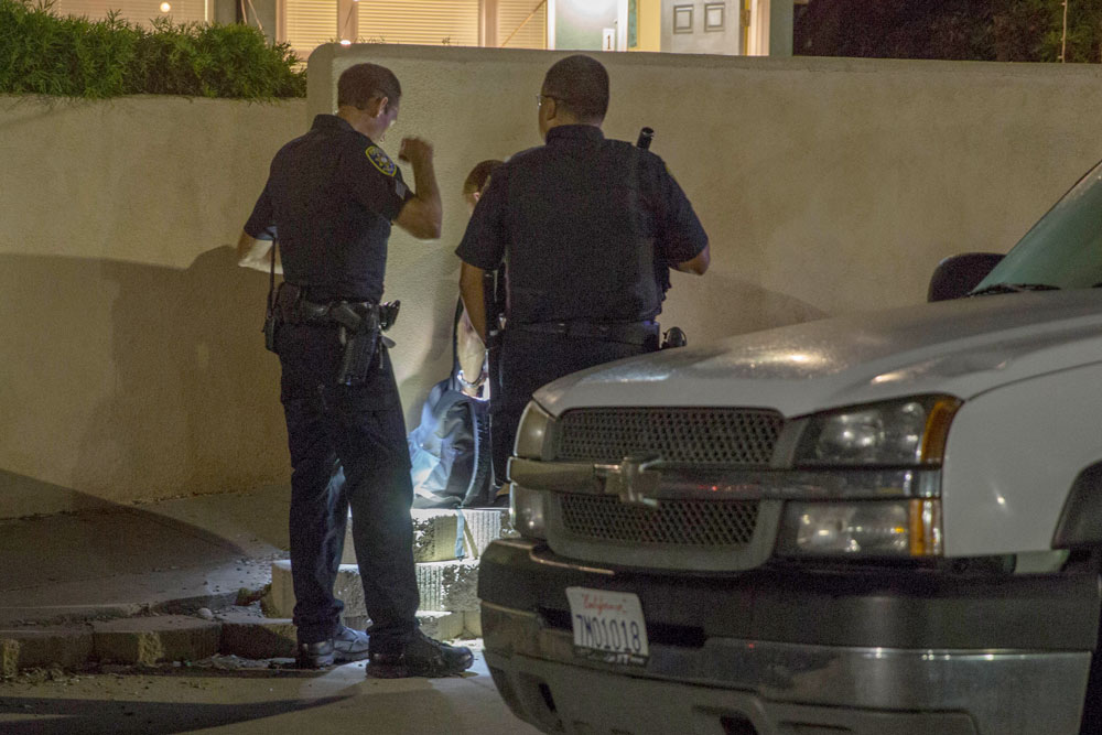 Officers interview suspects detained Saturday night after an altercation in which a UCSB police officer was injured. A Santa Barbara City College football player was arrested for allegedly injuring the officer, who suffered a concussion.