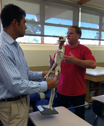 San Marcos High School Health Academy teacher Rick Ceriale, right, explains to Assemblyman Das Williams how students use clay to mold the muscle tissue on small mannequins.