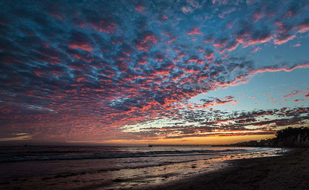A vibrant sunset Monday evening turns the clouds pink over Haskell's Beach in Goleta. (Sue Cook photo)