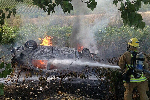 Santa Barbara County firefighters work to extinguish a car fire after the vehicle crashed into a vineyard while traveling on Highway 101 near Los Alamos on Sunday. There were no injuries but the car was a total loss.