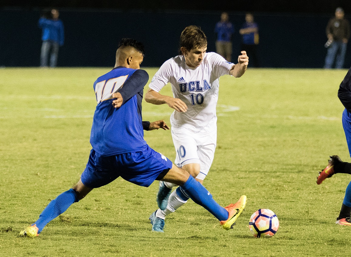 UCSB's Jose España pokes the ball away from UCLA's Brian Iloski during Saturday's game before 4,100 at Harder Stadium