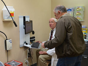"The three Santa Barbara Neighborhood Clinics have moved to electronic health records, an expensive requirement of the Patient Protection and Affordable Care Act. At a recent appointment, Dr. Charles Fenzi explains to patient Charles Condelos how his prescription can be sent paperless, and instantly, to the pharmacy of his choice. The system double-checks prescriptions against the patient's age, other drugs and condition, asking the doctors if they're sure. ""We're supposed to know that, but it's a good reminder,"" Fenzi says. (Lara Cooper / Noozhawk photo)"
