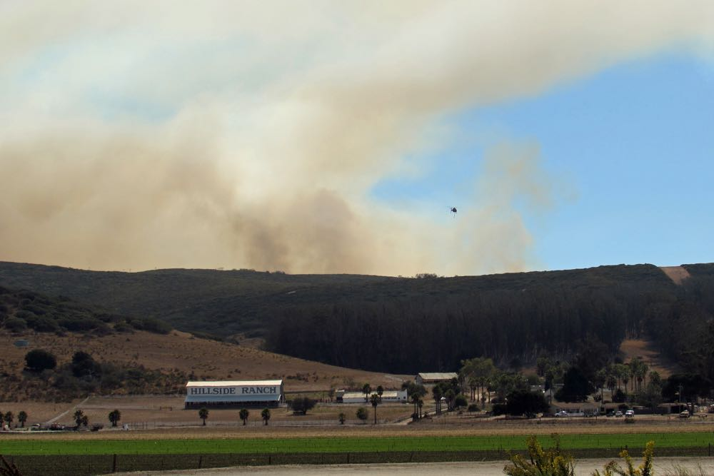 Smoke billows up behind Hillside Ranch near Lompoc on Sunday afternoon.