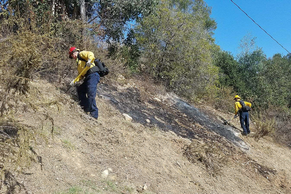 Santa Barbara firefighters extinguish a small brush fire on the Cleveland Elementary School campus Monday afternoon.
