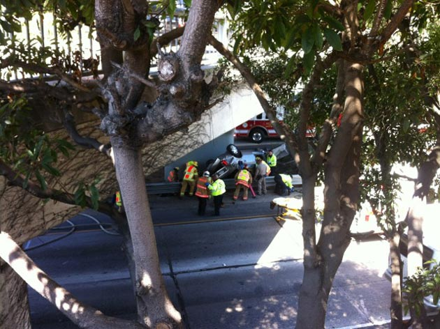 Montecito Fire Protection District crews work to extricate a person from a vehicle that rolled over on Highway 101 at the Olive Mill bridge in Montecito on Thursday after hitting a guardrail. The vehicle became wedged between the rail and the bridge support. (Harry Rabin photo)