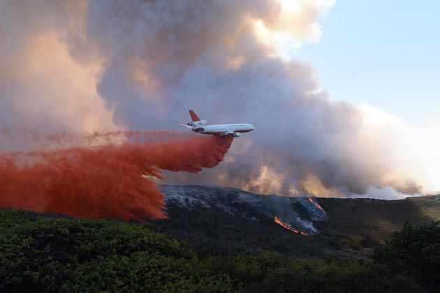 A firefighting aircraft bombs Vandenberg Air Force Base ... with fire retardant during the Canyon Fire on Sept. 20. (Staff Sgt. Shane Phipps / U.S. Air Force photo)