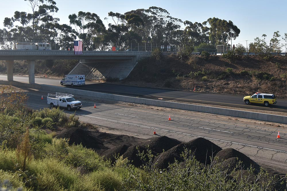 At the Winchester Canyon overpass, a Santa Barbara County Fire Department engine crew hung an American flag over Highway 101 as a procession passes for a Ventura County firefighter who died in a rollover crash near Lompoc earlier Wednesday.