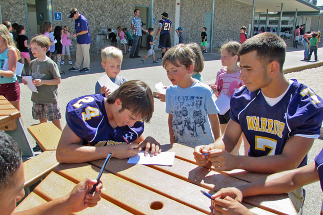 Righetti High School varsity football players Gian Solis, left, and Mitchell Silva sign autographs for young fans Thursday at Ralph Dunlap Elementary School in Orcutt.