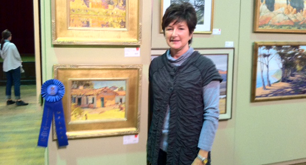 <p>Museum League volunteer Randee Winitzky, in charge of the indoor art exhibits at ArtWalk, presented by the Santa Barbara Museum of Natural History, stands next to first-place winner <i>At the Presidio</i>.</p>