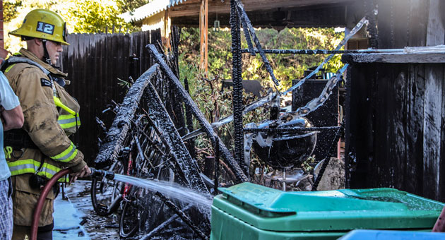 <p>A firefighter pours water on the remains of a shed that burned Saturday in Goleta, damaging two nearby homes.</p>