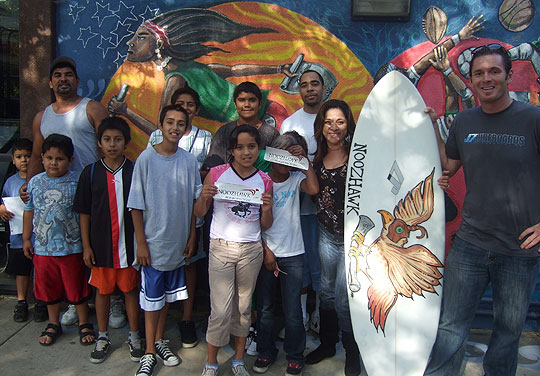 Surrounded by happy campers, Magda Arroyo shows off her new J7 Noozhawk surfboard at the Westside Boys & Girls Club. Noozhawk's Doug Elder, at right, delivered the presentation Monday.