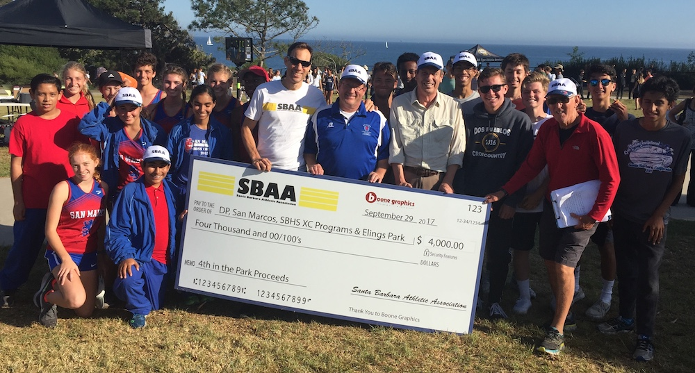 Santa Barbara Athletic Association President John Lofthus presents a check to the local high school cross country coaches at Friday's Dos Pueblos Invitational at Shoreline Park.