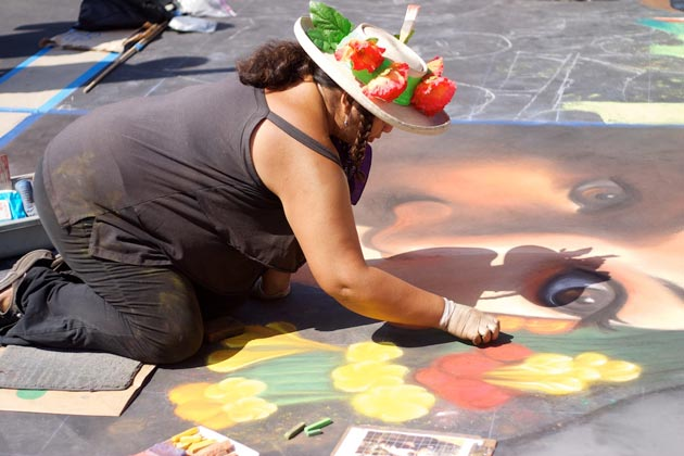 Chalk artist Cecelia Linayao lives in San Diego but makes sure she participates each year in Santa Barbara's I Madonnari Festival. On Sunday, she wore a hat adorned with poppies in honor of Memorial Day. Veterans' service is 'the the reason we're all able to do this today,' she says. (Jordon Niedermeier / Noozhawk photo)