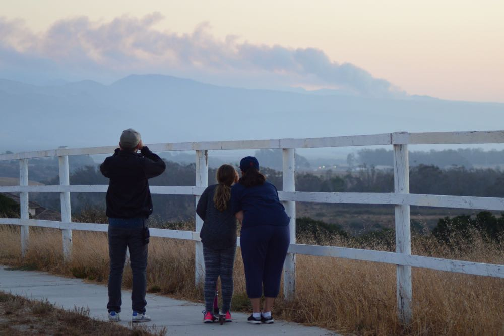 Spectators in Vandenberg Village watch smoke rise on the horizon from a brush fire burning Saturday evening on Vandenberg Air Force Base. The blaze is burning on VAFB's South Base area.