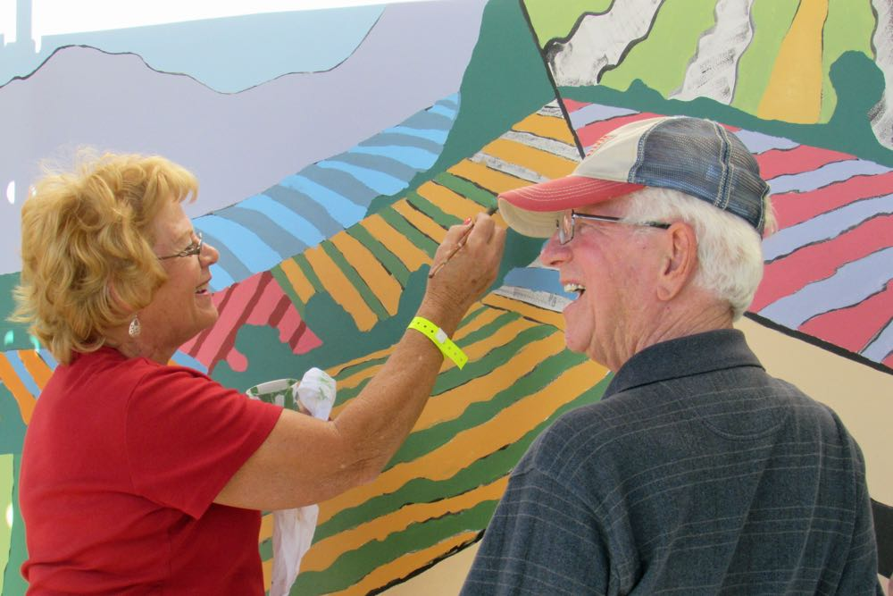 Former Lompoc residents Judy and Gene Stevens add paint to Lompoc's newest mural Saturday. The idea to add murals to the city's landscape came after then-Mayor Stevens and his wife saw a small British Columbia community's success with big art.
