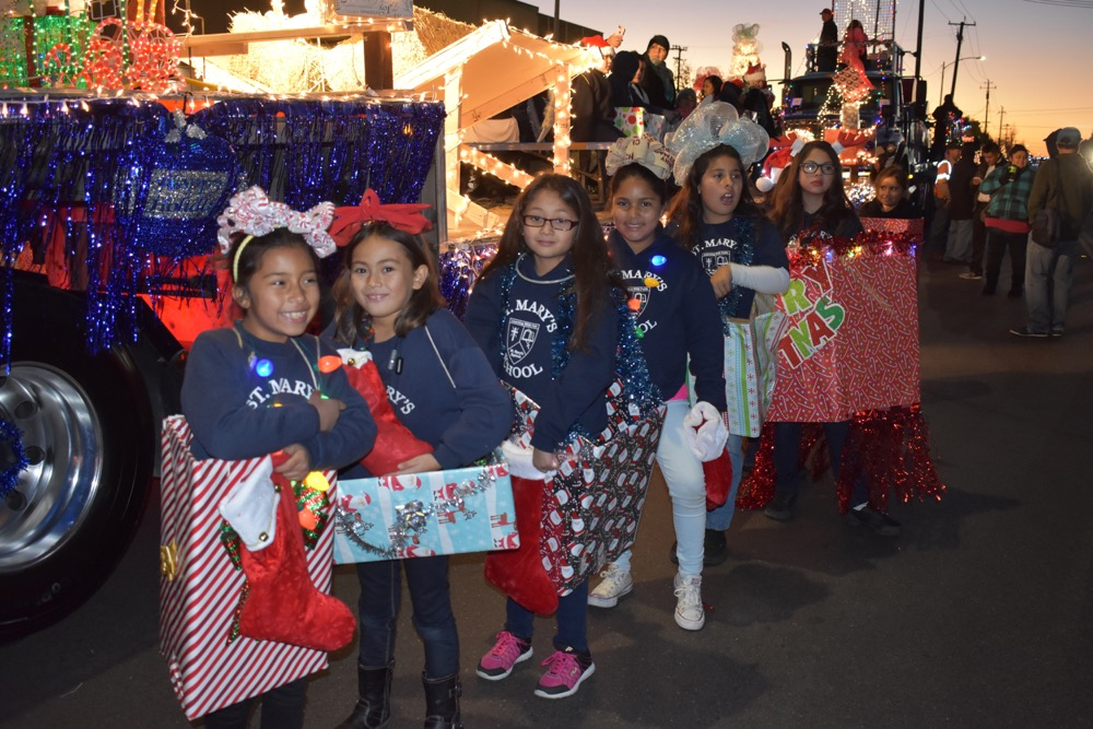Dressed as Christmas presents, students from St. Mary of the Assumption School line up next their float while awaiting the start of the Santa Maria Parade of Lights on Saturday evening.