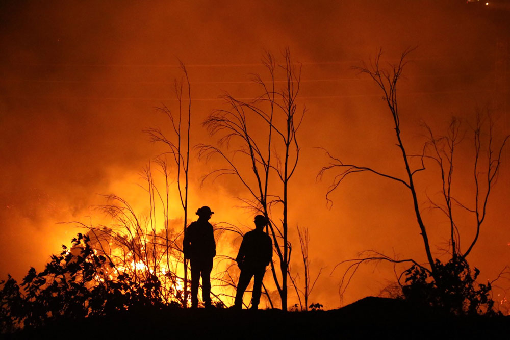 FIrefighters are silhouetted against the Thomas Fire at Parma Park above Santa Barbara the night of Dec. 16. (Ray Ford / Noozhawk photo)