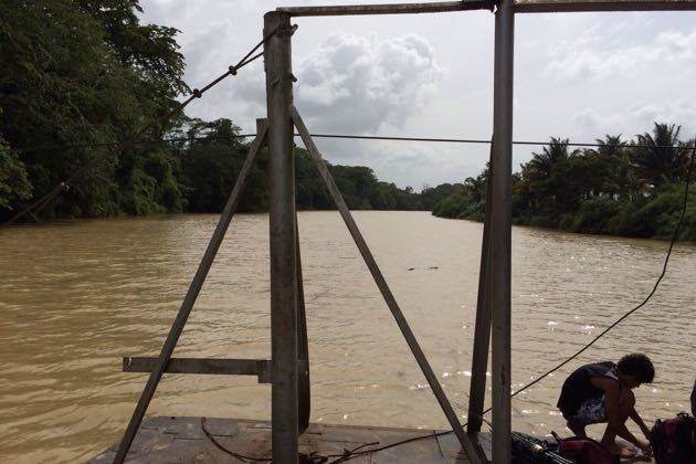 A boy fishes from a car ferry on the Belize River near Spanish Lookout in Belize. (Blake Dorfman photo / Laguna Blanca School)