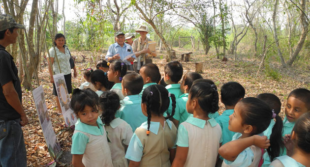 Students from Santa Familia Village, Cayo Belize, are welcomed to Känan K'aax, a model school garden in El Pilar Archaeological Reserve.