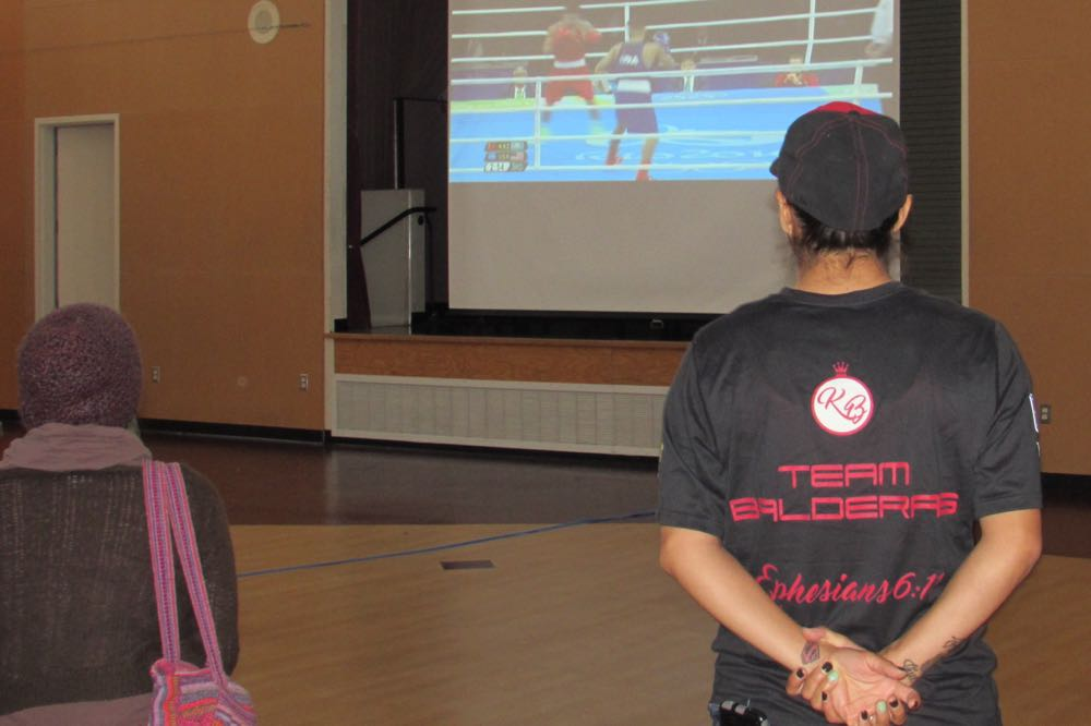 Maggie Suarez sports a T-shirt supporting Santa Maria boxer Carlos Balderas as his fight is broadcast at the Abel Maldonado Community Youth Center during the Summer Olympics.