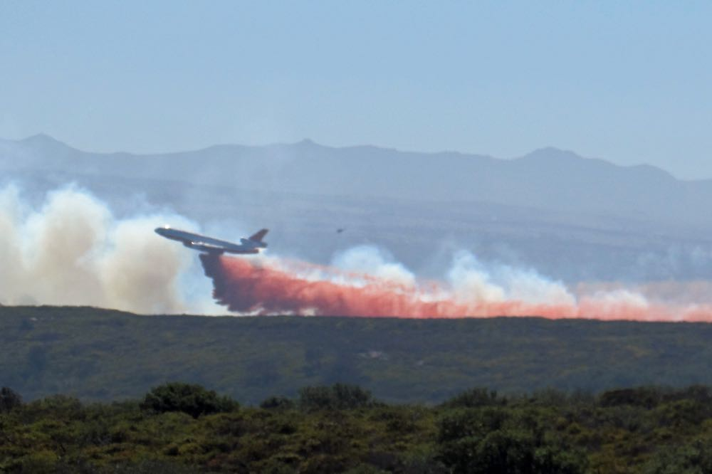 A firefighting aircraft makes a retardant drop on a blaze burning Friday afternoon on Vandenberg Air Force Base.