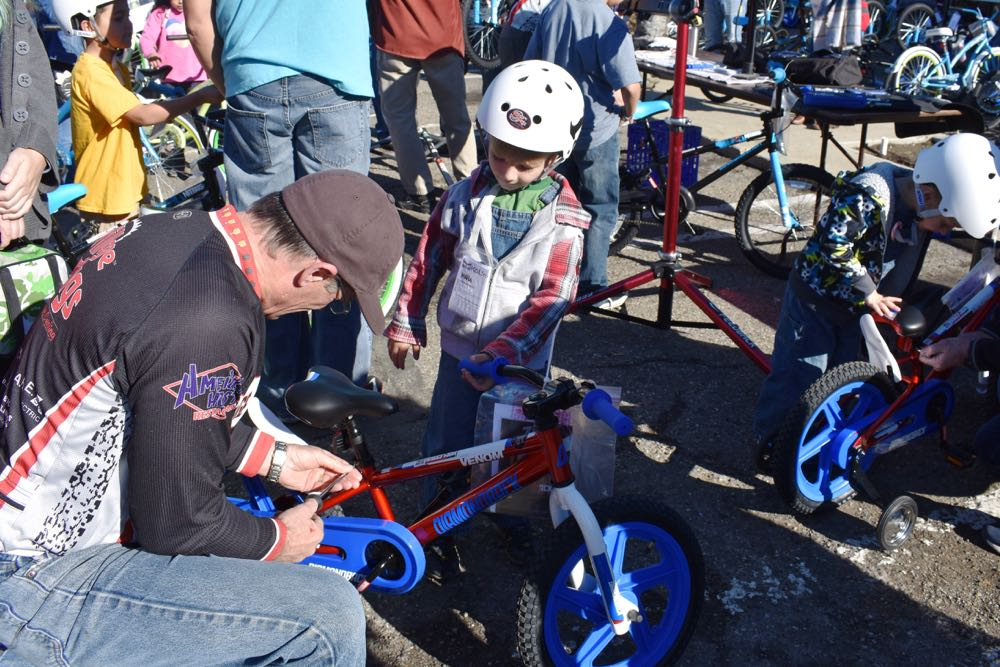 A child watches as a Village Dirtbag member adjusts a bicycle seat and handlebars during Saturday's annual giveaway of bikes for children of deployed military forces.