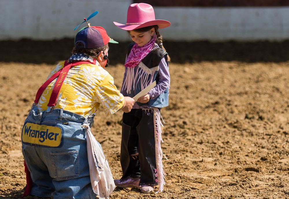 "Rodeo clown Charlie ""Too Tall"" West with the winner of the Best Dressed Cowgirl contest."