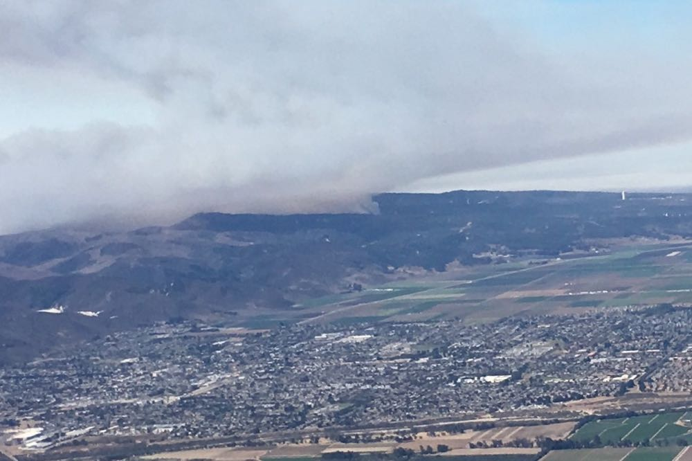 Smoke from the Canyon Fire on Vandenberg Air Force Base rises in the distance in an aerial photo taken over Lompoc on Sunday morning.