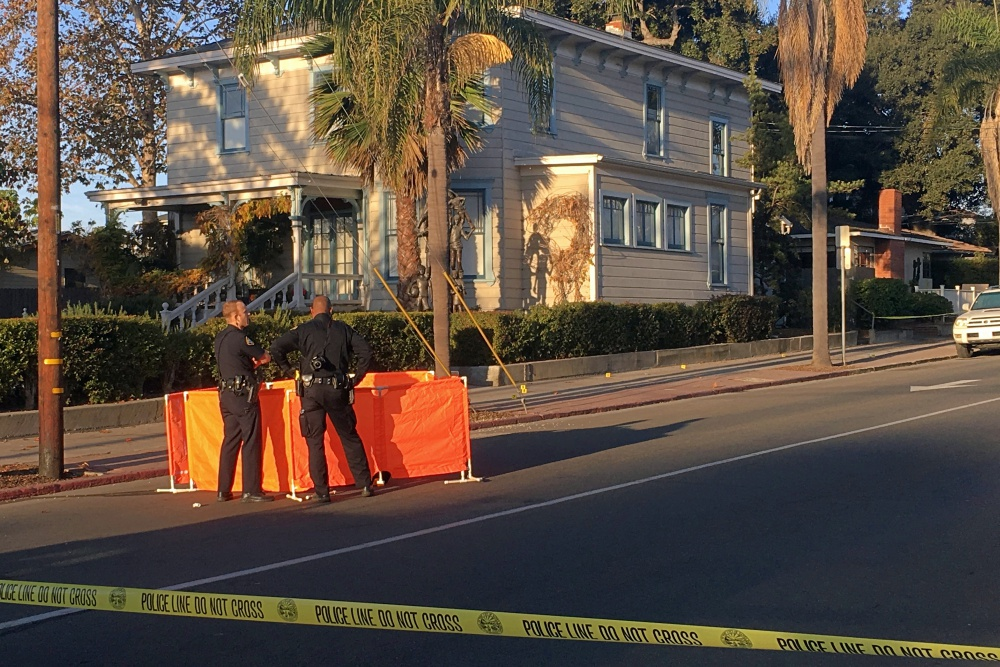 Santa Barbara police officers stand watch Monday morning at the scene of a fatal shooting in the 1300 block of De la Vina Street, between Sola and Victoria streets.