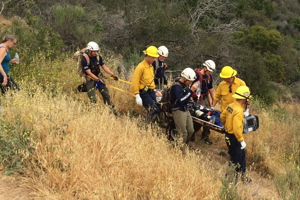 Rescue personnel carry an injured hiker down the McMenemy Trail in the Montecito foothills Friday afternoon.