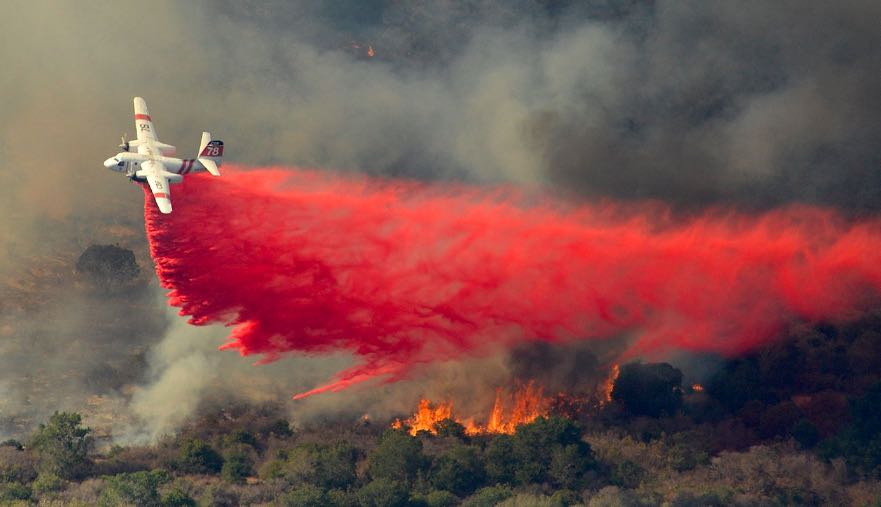 A CalFire S-2T makes a Phos-Chek drop on the Canyon Fire on Vandenberg Air Force Base on Sunday afternoon.