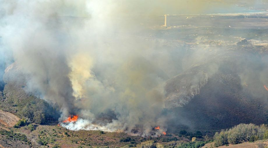 With Space Launch Complex-3 and the Pacific Ocean in the background, the Canyon Fire burns Sunday afternoon on Vandenberg Air Force Base.