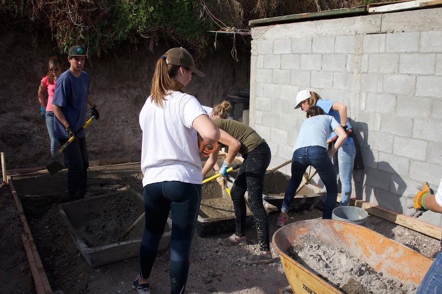 Students mix concrete for a foundation.