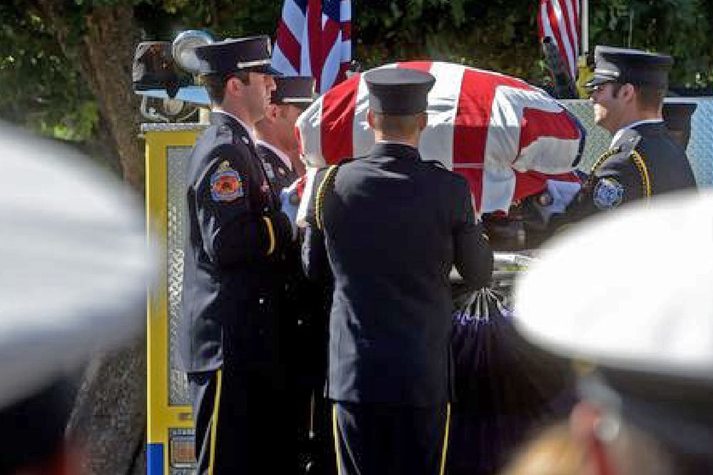The flag-draped casket of Ryan Osler, a Ventura County firefighter who was killed in a vehicle accident en route to a fire at Vandenberg AFB, is removed from a fire truck Monday prior to his funeral in Westlake Village.