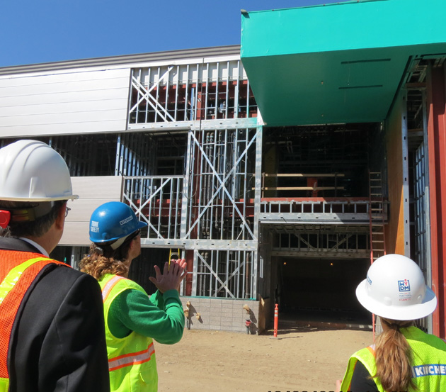 <p>Kitchell project manager Chris Young, center, leads Allan Hancock College staff on Monday into the soon-to-be main entrance of the One Stop Student Services Center.</p>