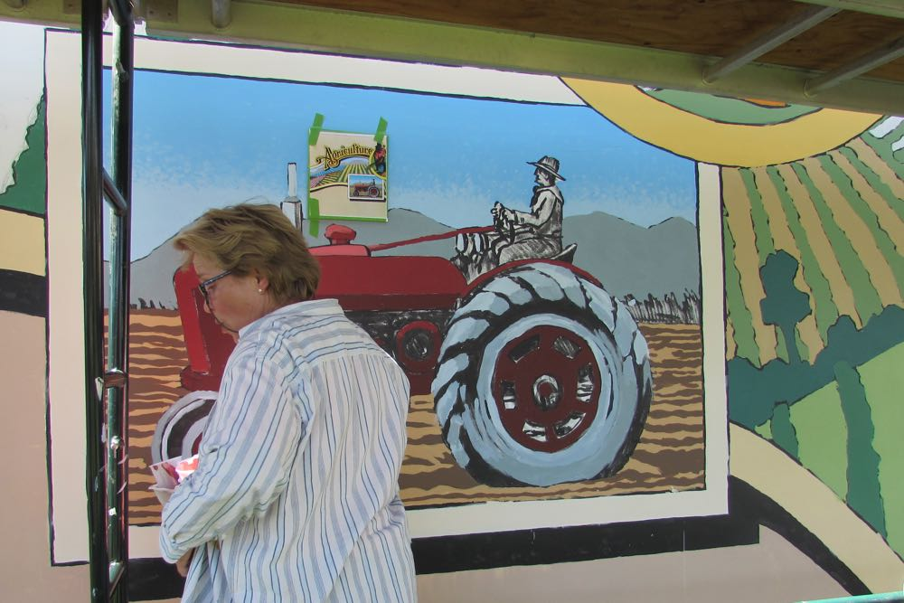 Ann Thompson, Lompoc Mural Society curator, fine-tunes a tractor that is part of the Lompoc community's newest mural.
