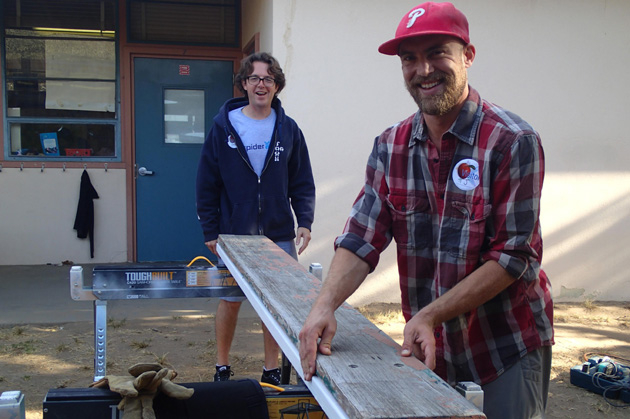 Church volunteers assist with refurbishing student lunch tables.