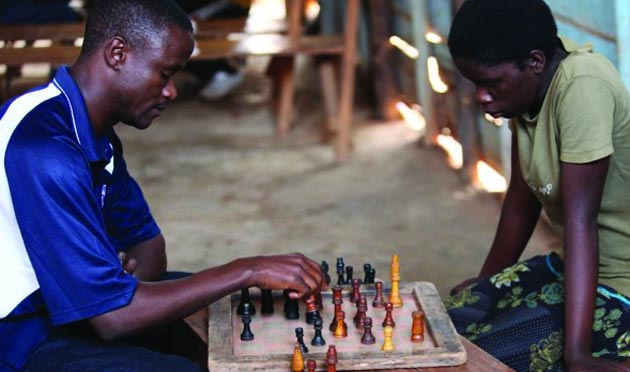 Robert Katende, left, at the chessboard in Katwe, Uganda, with Phiona Mutesi, the girl who he believed he could teach to become a prophet and eventually a national chess champion. (David Johnson photo / Silentimages.org)