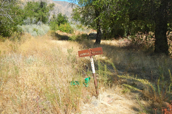 An iron sign marks the end of Judell Canyon Trial at the rustic Heath Camp.