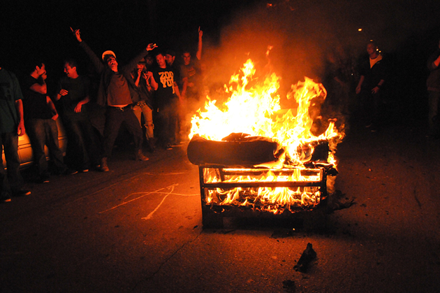 Revelers in Isla Vista in 2011 gather around a loveseat seat ablaze in the middle of Del Playa Drive. County firefighters were called to the scene and extinguished the couch fire. (Lara Cooper / Noozhawk file photo)